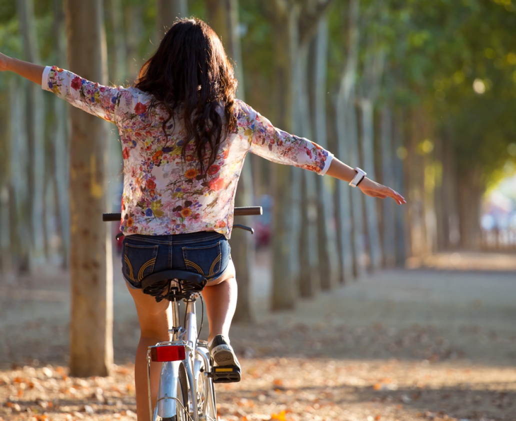 Outdoor portrait of pretty young girl riding bike in a forest.
